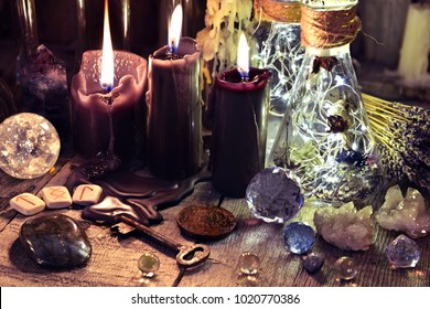Magic crystals, ritual objects, runes, black candles and bottles on witch table. Occult, esoteric and divination concept.