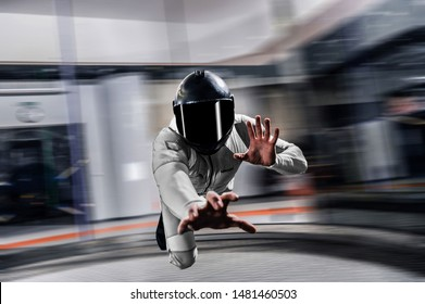 Magic fly. Men fly and show ten fingers. Free fall in Indoor skydive. Skydiver in white suit