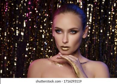 Magic Girl Portrait in Gold. Golden Makeup, close-up portrait in studio shot, color.