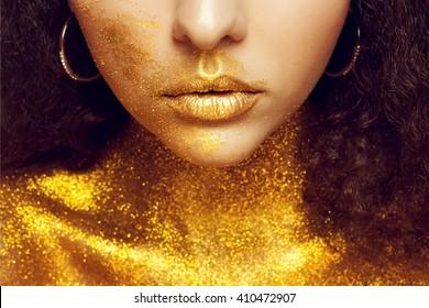 Magic Girl Portrait in Gold. Golden Makeup, close-up portrait in studio shot, color