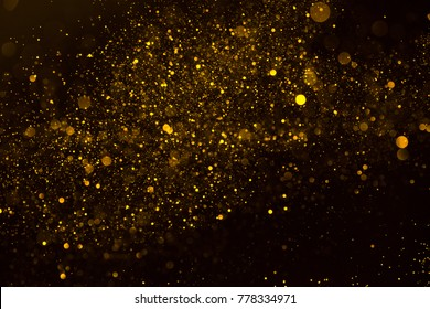Magic glowing gold dust particles flowing abstract background