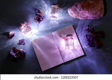 Magic light flatlay with glow and creative book, ultraviolet color