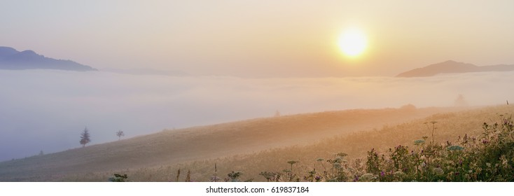 Magic misty sunrise in the mountains. Panoramic view.