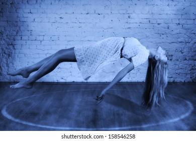 Magic moment - girl levitates on a brick wall background