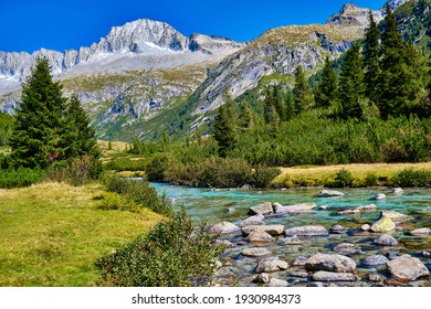 Magic montain river with summer mountains in Val di Fumo, in Adamello-Brenta National park. Blue sky upon a beautiful italian Dolomites mountains landscape with forest. Italian tourism