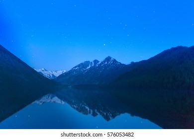 Magic night landscape with mountains, frozen lake and amazing starry sky.