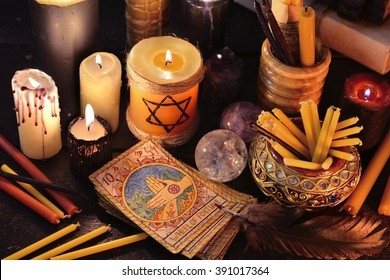 Magic objects, candles and the tarot cards in candle light.  Fortune telling seance or black magic ritual. Scary still life with occult and esoteric symbols. Halloween or divination rite