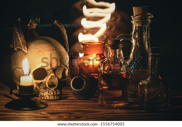 Magic potion bottle on the table and mystic light around. Witchcraft. Alchemistry concept.