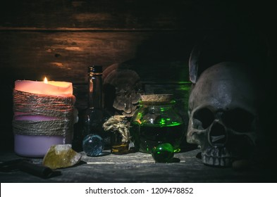 Magic potion and human skull on magic table background. Witchcraft concept.