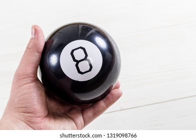 Magic prediction eight ball in hand, on the white background.