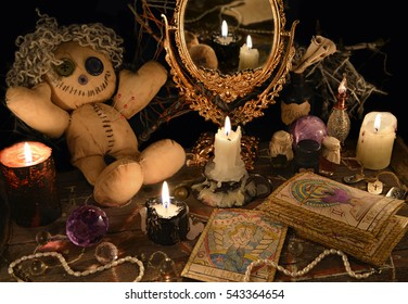 Magic ritual with voodoo doll, mirror, candles and tarot cards. Halloween concept, mystic or divination spell with occult and esoteric symbols. Vintage objects on witch table