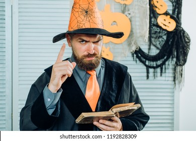 Magic, spell, book of magic. Bearded magician reads an old book about magic. Halloween Wizard