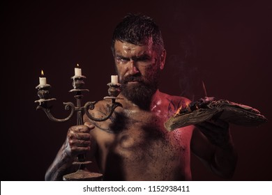 Magic spell, enchantment, witchcraft. Hipster man with book and candles burning on purple background. Might, mystic, knowledge. Halloween holidays celebration. Wizard, sorcerer warlock