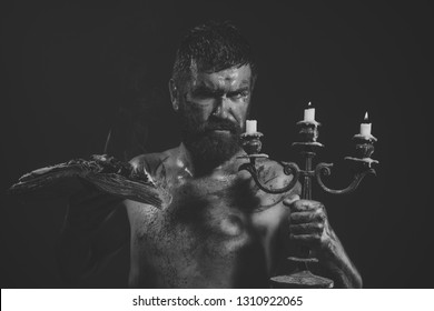 Magic spell, enchantment, witchcraft. Hipster man with book and candles burning on purple background. Might, mystic, knowledge. Halloween holidays celebration. Wizard, sorcerer, warlock.