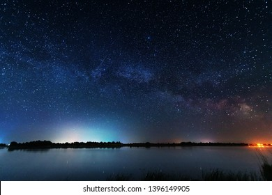 Magic starry night with the galaxy Milky way near the river with a large tree.