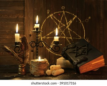 Magic still life with burning candelabrum, evil candles, witch books and quill against background with pentagram. Black magic ritual with occult, evil and esoteric symbols. Scary halloween rite