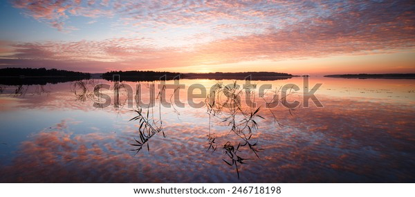 Magic sunrise panorama with bright saturated sky perfectly reflected in still water