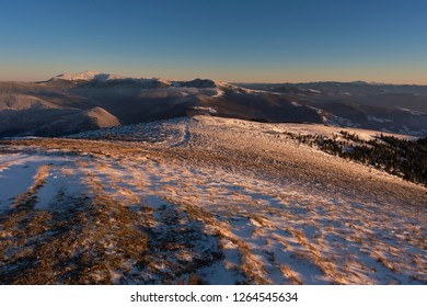 Magic sunset on the high mountains of the Ukrainian Carpathian Mountains, brilliant structure of frozen snow at strong winds