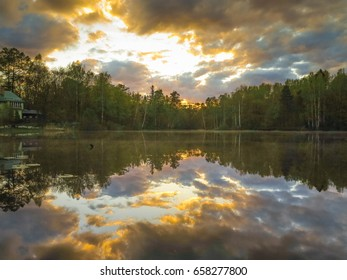 The magic sunset reflects in the mirror of the forest lake in complete calm