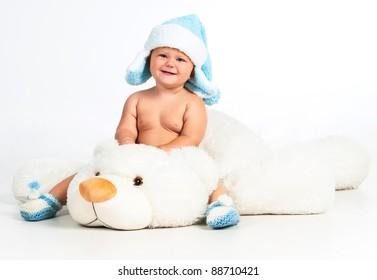 Magic winter: cute little boy sitting on a white teddy bear