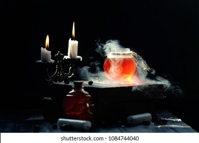 Magic and wizardry concept. Set of sorcery book, magic potions and candles on table. Health potion with vapor streaming from bottle. Alchemy concept.