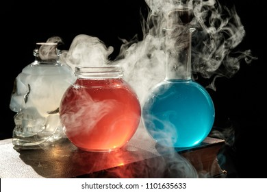 Magic and wizardry concept. Set of sorcery book, magic potions and candles on table. Health and mana potion. Alchemy concept.