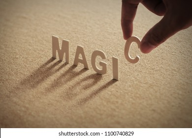 MAGIC wood word on compressed or corkboard with human's finger at C letter.