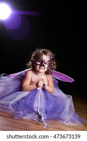 Magical! Adorable toddler wearing a long tutu dress, butterfly wings and mask and holding a silver wand. Background light and lens flare for dramatic effect.