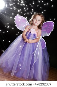 """Magical! Adorable toddler wearing a long tutu dress, butterfly wings and holding a magic wand. Background light and """"sparkles"""" for effect."""