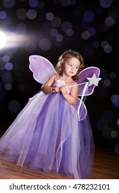 """Magical! Adorable toddler wearing a long tutu dress, butterfly wings and holding a magic wand. Background light, lens flare, and """"sparkles"""" for effect."""