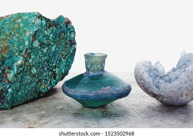 Magical alchemical ancient bottle, crystal, and Chrysocolla photographed on white. Celestite, also known as Celestine, is valued for its high frequency and Divine energies.
