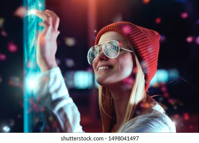 A magical approach to the smart city concept. A beautiful young millennial hipster girl is using an application interface by touch screen out in the street. Communicate about future tech