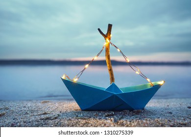 magical blue paper boat with lantern at the beach - romantic evening