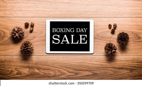 Magical Boxing Day Sale theme background, pine cones and digital tablet on wooden table