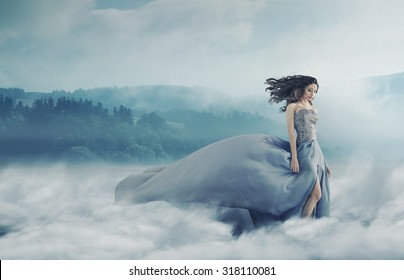 Magical brunette lady on a foggy field