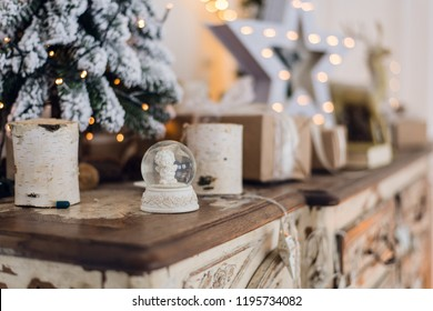 Magical Christmas snow globe with little angel statue inside. Christmas decoration around. Shallow depth of field with selective focus on snowglobe.