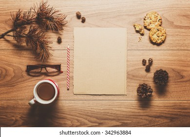 Magical christmas theme background, pine cones, coffee, cookies and an empty letter to santa on wooden table