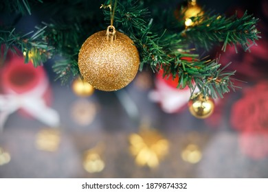 Magical Christmas - x-mas tree close-up, green pine branches with shiny, traditional gold and red ornaments. Christmas tree with presents, dark blurry background for a wallpaper, poster, holiday card. - Shutterstock ID 1879874332