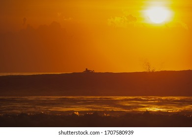 Magical dramatic sunset on a tropical beach. Seascape, ocean waves and bright clouds in the sky. Golden hour. Rest on the seashore, beach vacation. Concept.