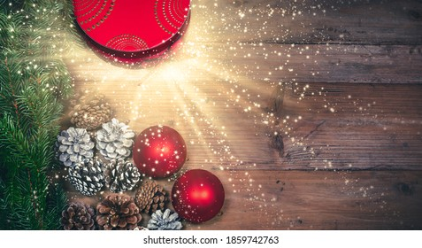 Magical exploding Christmas gift box and decoration background.  Top view of a red gift box with exploding fireworks, luminous rays and sparkling glitter stars.