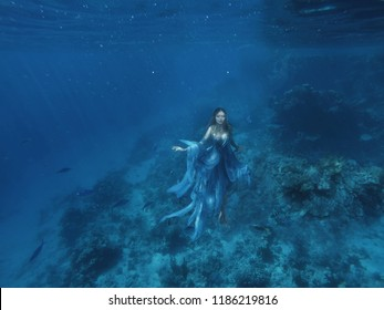 a magical fairy mermaid in a blue flying light dress floats on the ocean floor, sea queen and jellyfish, a halloween image, a photo under water in the red sea, a water nymph or a drowned woman. art