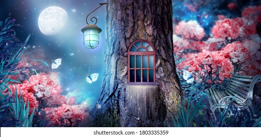 Magical fantasy elf or gnome house in tree with window and lantern, bench in enchanted fairy tale forest with fabulous fairytale blooming pink rose flower garden and shiny glowing moon rays in night - Shutterstock ID 1803335359