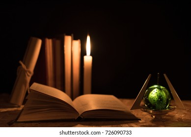 A magical green ball, a scroll, a candle with a flame and an old book in the dark of the night