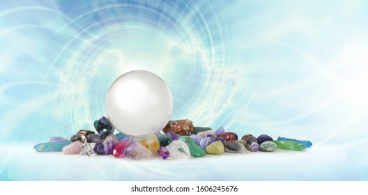 Magical Healing Crystal Vortex Background - a large clear crystal ball atop a selection of healing crystal stones against a pale blue spiralling vortex with copy space