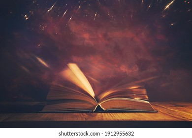 Magical image of open antique book over wooden table with glitter overlay