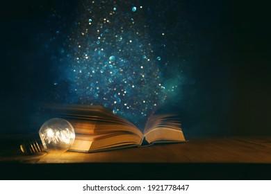Zauberhaftes Bild eines offenen antiken Buches auf Holztisch mit glänzendem Hintergrund