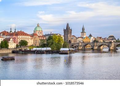 A magical landscape of the Charles Bridge and St. Nikolaus Church in Prague over Vltava river, Czech Republic