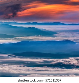 Magical landscape in the mountains at sunset. View of  colorful sky with clouds and foggy hills covered by forest.