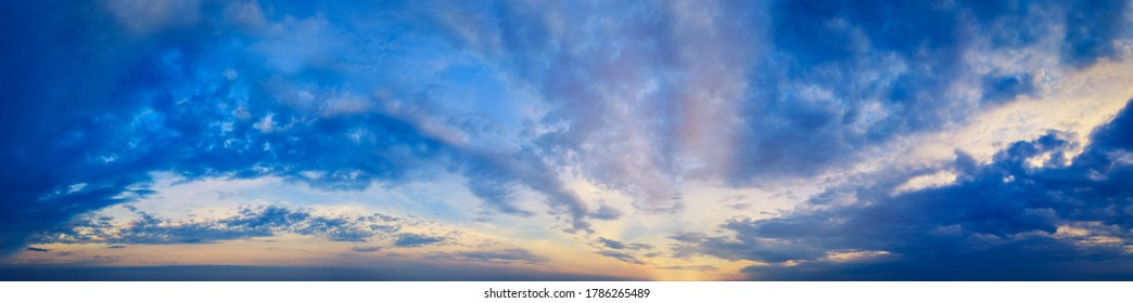 Magical Magnificent Blue Sky panorama at Cloudy sunset with sun rays and warm clouds - Ultra-wide banner.