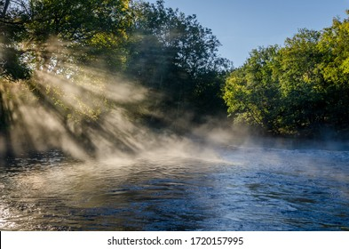 Magical morning with fog and sunshine at Säveån, a river just outside Gothenburg, Sweden. View of a beautiful landscape, with trees, water, morning light and mist. Natural background with copy space.